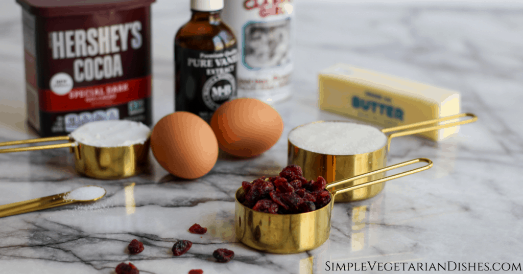 ingredients on marble table eggs cocoa flour sugar salt baking powder dried cranberries butter