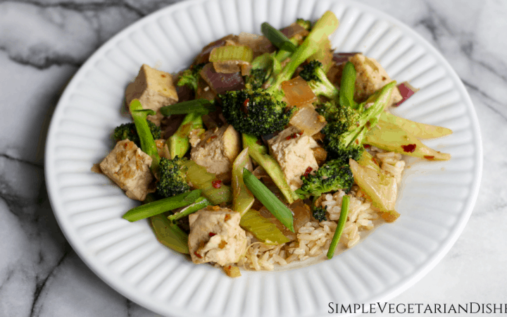 Sichuan broccoli and tofu with celery, green and red onions, and brown rice served on white plate on white marble table