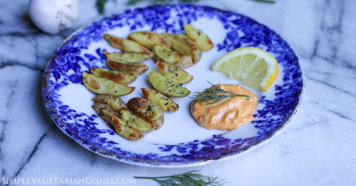 harissa aioli with roasted potato wedges served on blue china with lemon wedge on white marble table