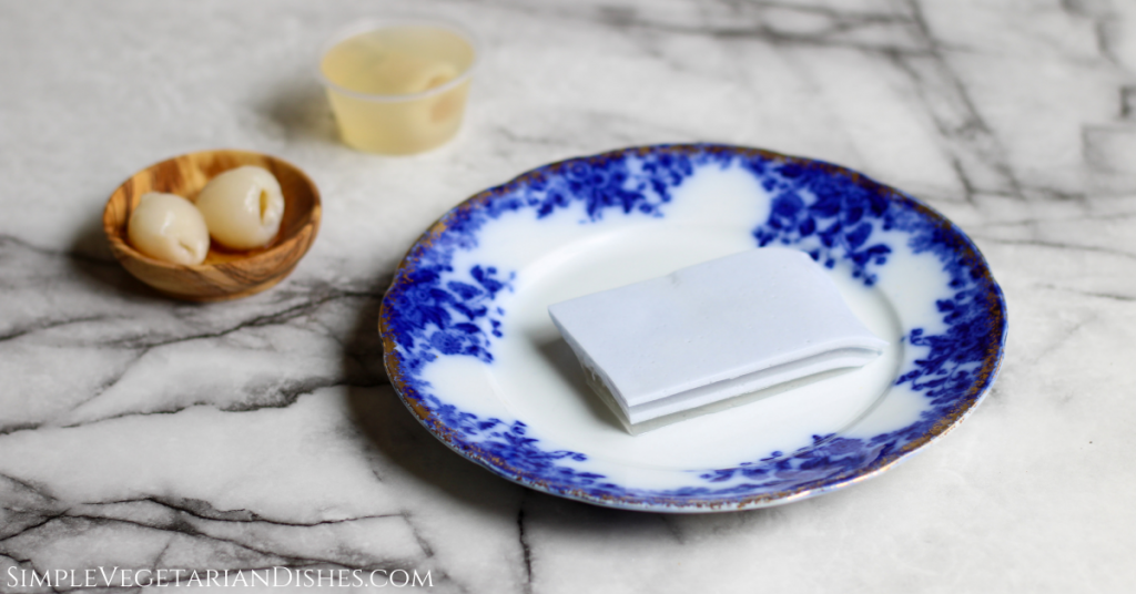 lychee jelly layered with coconut jelly served on blue china with lychees in background