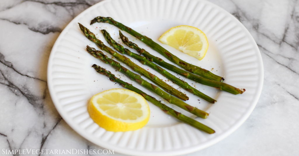 smoked asparagus served with lemon slices on white plate