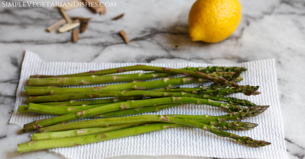 washed and trimmed asparagus on paper towel on white marble table with lemon in background