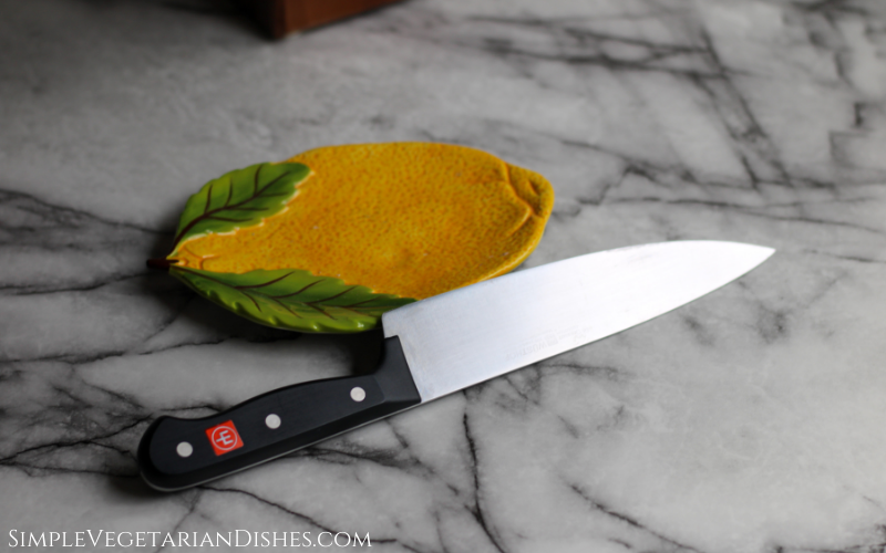 wusthof gourmet chef's knife propped on lemon plate on white marble table