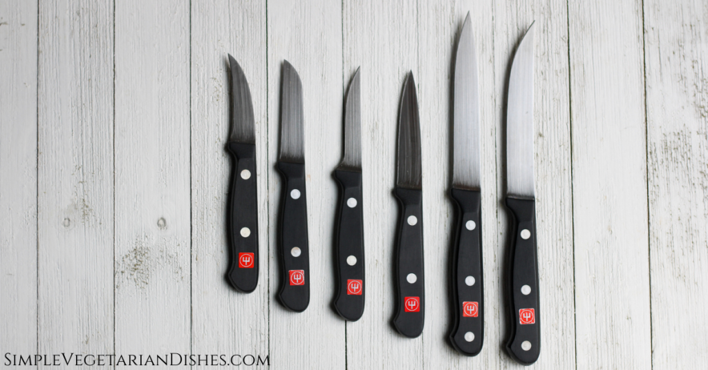 wusthof gourmet paring, peeling, trimming, spear-point paring, utility and steak knives on white board