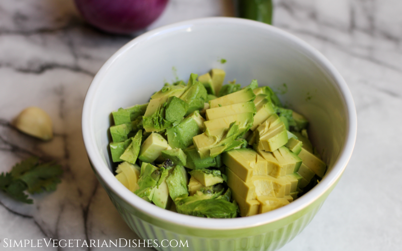 green mixing bowl full of avocado chunks on white marble table