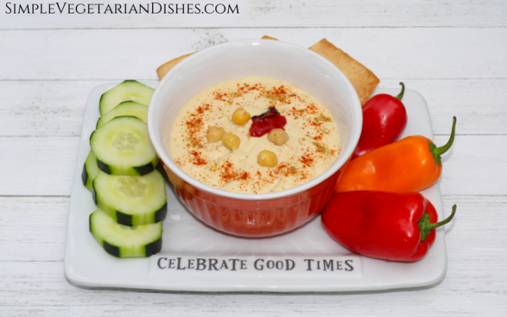 hommus served on white tray with red and orange peppers, cucumber slices and pita chips