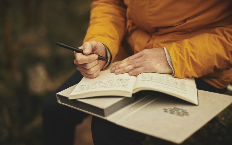 person in orange jacket writing in journal or planner