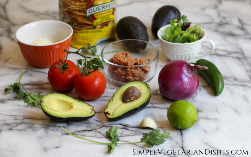 tostaguac ingredients on white marble table avocados, tomatoes, refried beans, cheese, onion, tostada shells, garlic, jalapeño, lettuce, cilantro