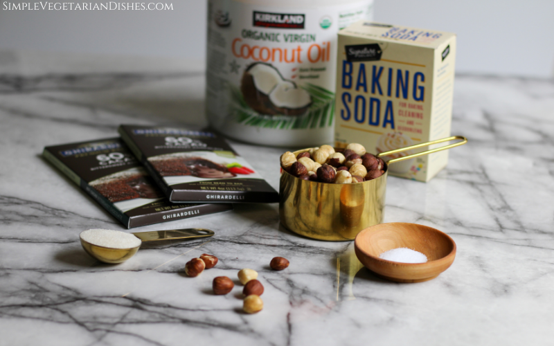 chocolate, hazelnuts, coconut oil, sugar, salt and baking soda on white marble table