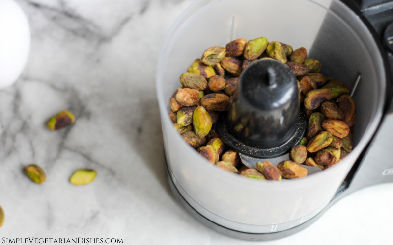 pistachios in food processor on white marble table