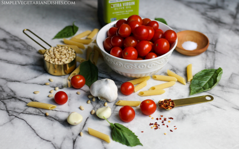 bowl of cherry tomatoes, penne, garlic, basil, salt, pine nuts, evoo, and crushed red pepper flakes on white marble table