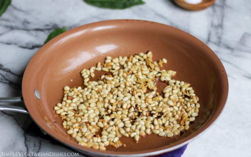 toasted pine nuts with fresh garlic, olive oil, and crushed red pepper flakes in copper skillet