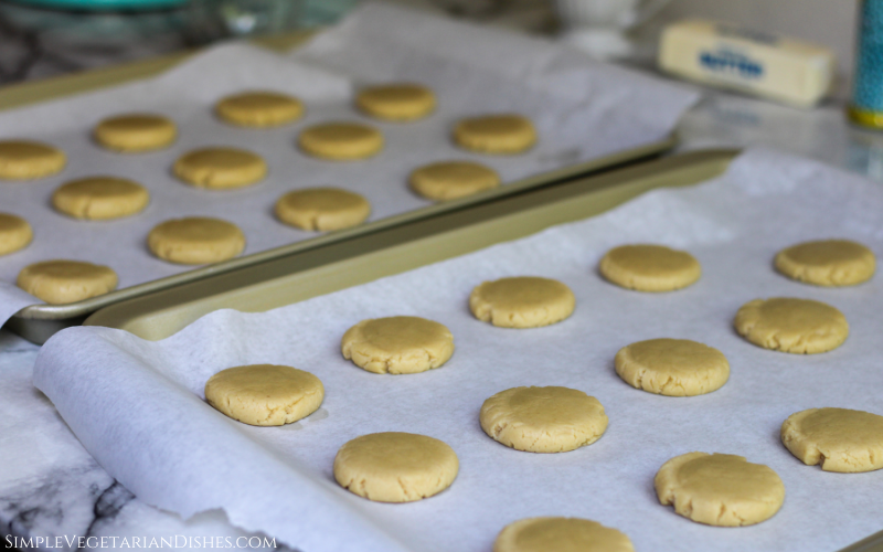 flattened cookie dough on parchment paper on gold cookie sheets