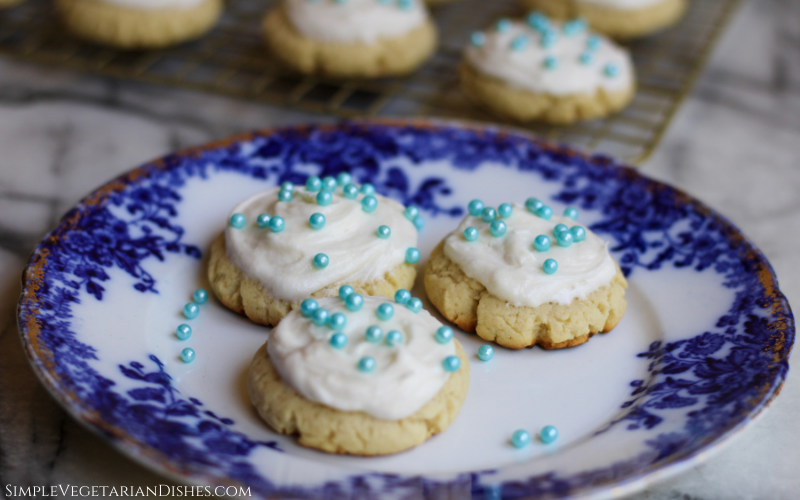close up of high altitude sugar cookies decorated with cream cheese icing and blue sugar pearls