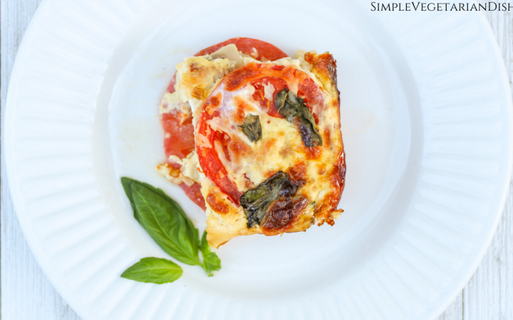 crustless tomato pie slice served on white plate on white board background garnished with fresh basil