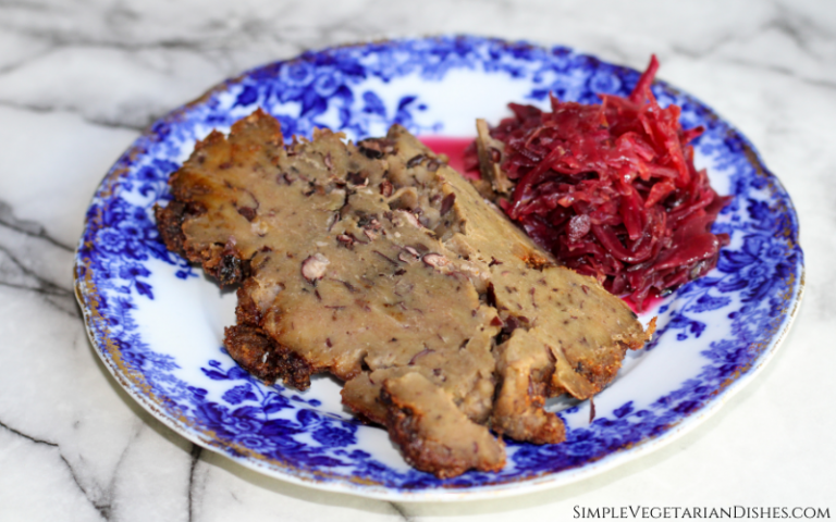 vegan corned beef served with red beet and cabbage kraut on blue china